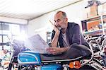Focused senior male motorcycle mechanic reviewing manual in workshop