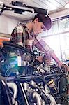 Female motorcycle mechanic repairing motorcycle in workshop