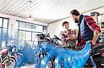 Male and female motorcycle mechanics repairing motorcycle in workshop