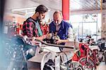 Male motorcycle mechanics repairing part in workshop