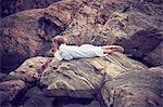 Boy lying on rocks