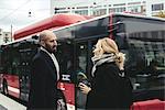 Business people talking on sidewalk by bus in city