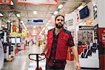 Salesman pulling handtruck in hardware store