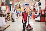 Portrait of salesman standing by handtruck in hardware store