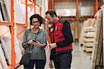 Salesman and female customer using smart phone in hardware store