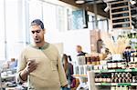 Man using smart phone supermarket