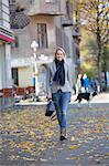 Pretty elegant woman walking with handbag in citycenter and smiling at camera