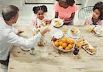 Multi-ethnic family eating breakfast at table