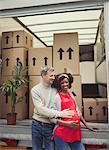 Portrait smiling pregnant multi-ethnic couple at moving van