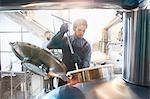 Male coffee roaster checking tank