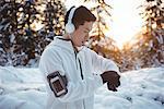 Smiling man adjusting time on smartwatch during winter
