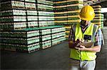Male worker writing on clipboard in warehouse