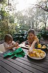 Two young sisters preparing lemons for lemonade at garden table
