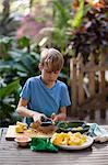 Boy preparing lemons for lemonade at garden table