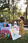 Girl buying lemonade from lemonade stand in garden