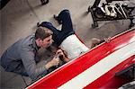 Overhead view of two men repairing in boat repair workshop
