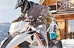 Couple riding snowmobile outside sunny cabin