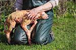 Farmer kneeling in the grass, holding a newborn lamb on her lap.