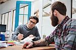Male designers making notes at design studio desk meeting