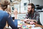Female and male designers at design studio desk meeting