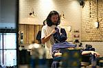 Hairdresser in barbershop wrapping customer in towel