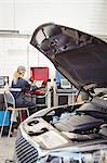 Female mechanic using laptop