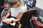 Female mechanic writing on diary