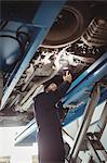 Mechanic examining a car with flashlight