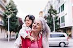 Mature woman giving girl piggyback in city