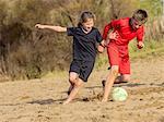 Girl and boy chasing soccer ball across sand
