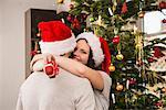 Woman holding Christmas gift hugging her husband