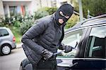 Thief breaking into a car using crowbar