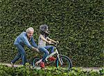 Grandmother pushing grandson on his bicycle