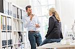 Male designer explaining idea to female colleague in creative studio meeting