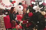 Sad young woman sitting alone on sofa at christmas