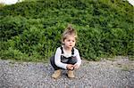 Cute girl crouching on dirt track looking away