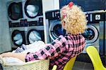 Woman watching washing machines in laundrette