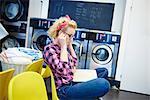Woman sitting in laundrette putting on earphones