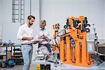 Two engineers looking at digital tablet in engineering factory