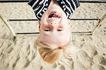 Portrait of boy hanging upside down over sand, smiling, Santa Barbara, California, USA