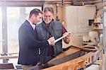 Male customer signing paperwork for finished wood kayak in workshop