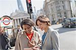 Smiling businesswomen with digital tablet talking on sunny urban city street