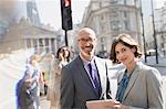 Portrait smiling, confident business people using digital tablet on sunny urban city street, London, UK