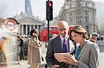 Business people using digital tablet on sunny urban city street, London, UK