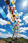 Rows of colourful prayer flags against blue sky, Zhagana, Gansu, China