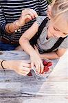 Mother and daughter having strawberries in garden