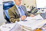 Businessman reading paperwork at office desk