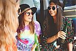 Three young boho women wearing sunglasses in recreational van