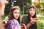 Young boho women eating melon slice at festival