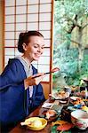 Caucasian woman wearing yukata eating at traditional ryokan, Tokyo, Japan